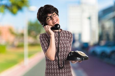 Girl with vintage look talking to vintage phone