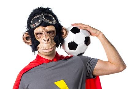 Superhero monkey man holding a soccer ball