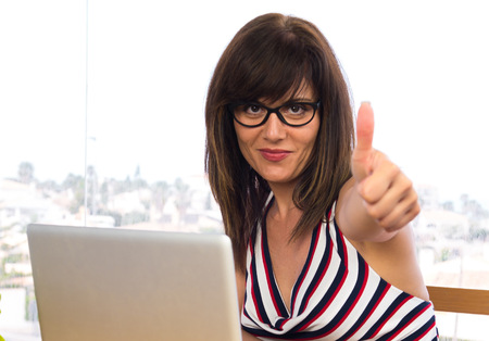 Business woman working with his laptot with thumb up Stock Photo