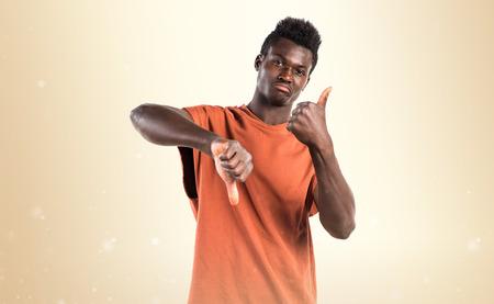 Handsome black man making good-bad sign Stock Photo
