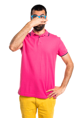 pinching: Man with colorful clothes doing smelling bad gesture Stock Photo