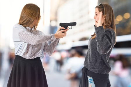 youth crime: Teen girl pointing with a gun Stock Photo