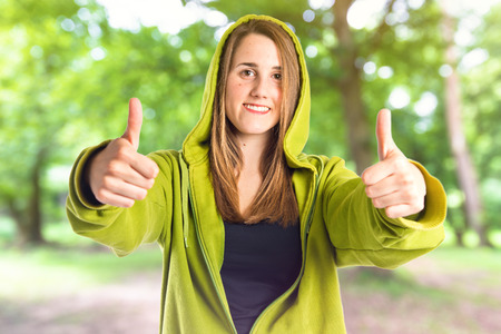 happines: Pretty young girl with thumbs up over white background Stock Photo