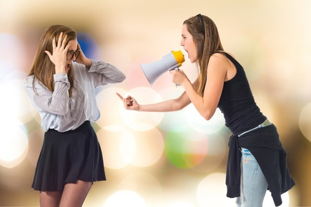 Girl shouting at her sister by megaphone Stock Photo