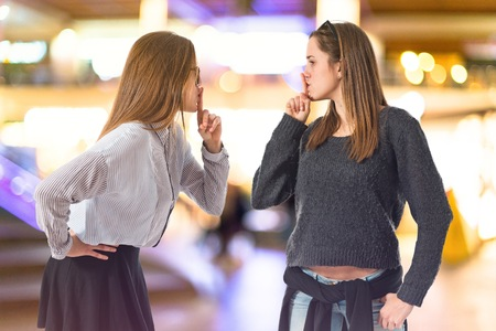 silence gesture: Twin sisters making silence gesture Stock Photo