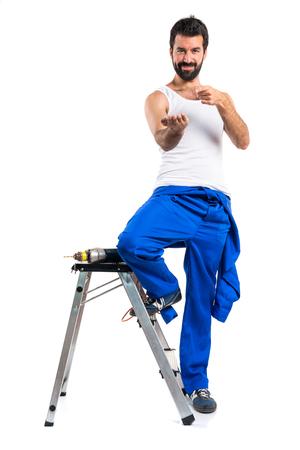 electricista: técnico eléctrico joven con un taladro y la celebración de algo