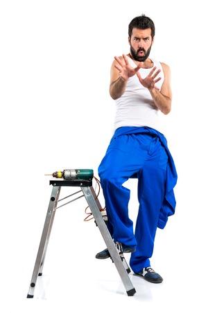 electricista: técnico eléctrico joven asustado con un taladro