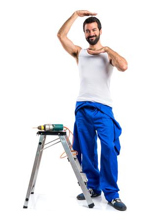 electricista: técnico eléctrico joven con un taladro y enfocando su cara