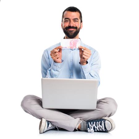 salarios: Man with laptop taking a lot of money