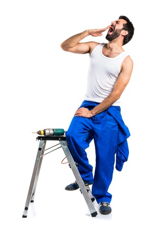 Young electrical technician with a drill yawning