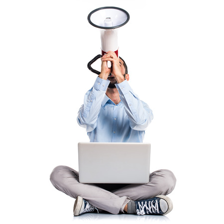Man with laptop shouting by megaphone