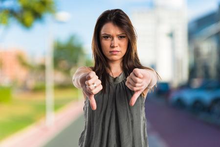 Young girl doing bad signal