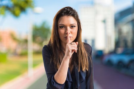 Young girl making silence gesture