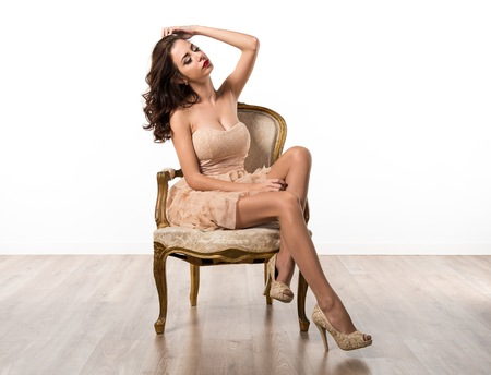 old furniture: Beautiful young model woman posing in studio on vintage armchair Stock Photo