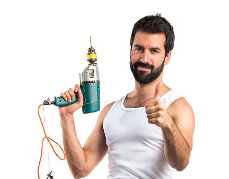 electricista: técnico eléctrico joven con un taladro con el pulgar arriba Foto de archivo