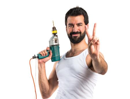 electricista: técnico eléctrico joven con un gesto de la victoria toma de perforación