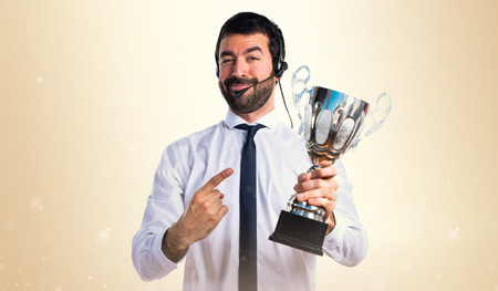 telemarketer: Handsome telemarketer man holding a trophy Stock Photo