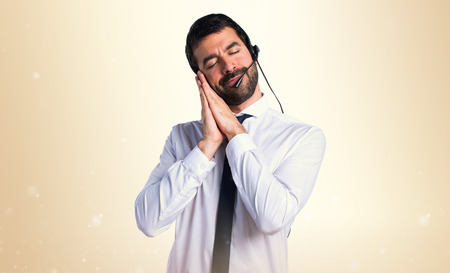 Young man with a headset doing sleep gesture Stock Photo