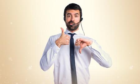 Handsome telemarketer man making good-bad sign