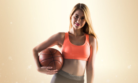 Blonde girl playing basketball