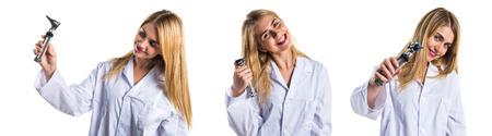 dolor de oido: Mujer del doctor con otoscopio Foto de archivo