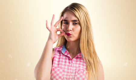 Blonde girl making silence gesture Stock Photo