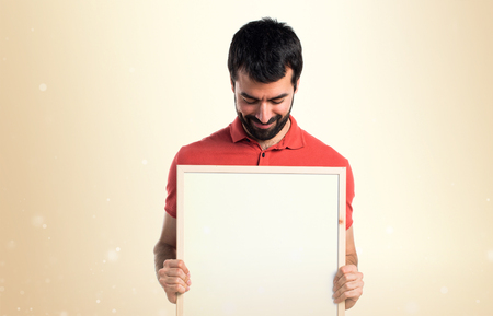 a placard: Handsome man holding an empty placard Stock Photo