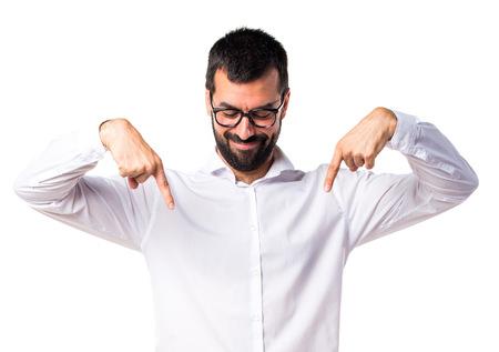 Hombre guapo con gafas apuntando hacia abajo Foto de archivo - 67430579