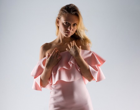 Pretty model woman posing in studio with a pink dress
