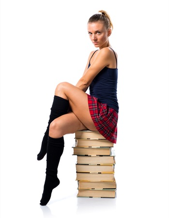 Pretty blonde school girl sitting on many books