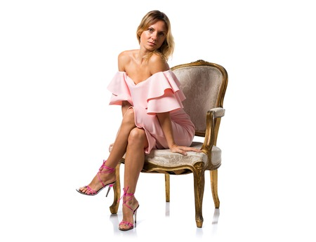 Pretty model woman posing in studio with a pink dress on vintage armchair