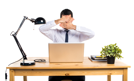 Businessman in his office covering his face