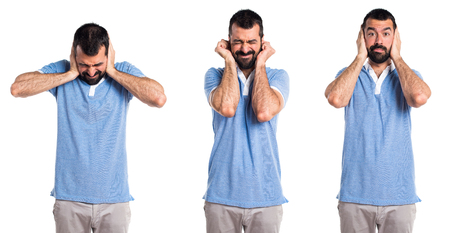 Man with blue shirt covering his ears