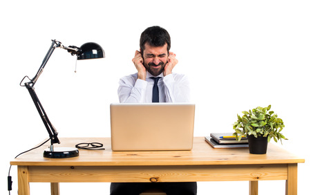Businessman in his office covering his ears Banco de Imagens - 69933414