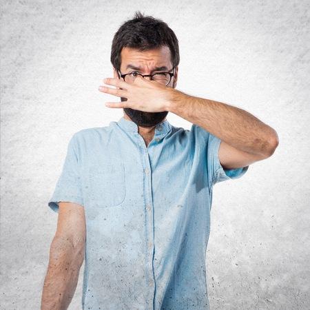 Handsome man with blue glasses making smelling bad gesture