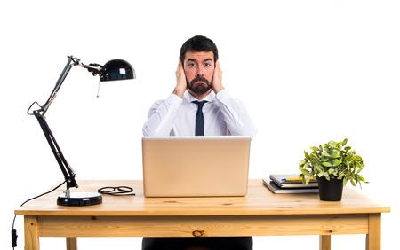 Zakenman in zijn kantoor om zijn oren