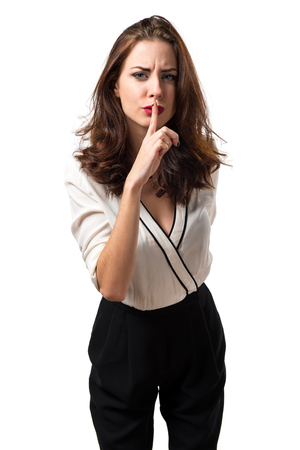 Beautiful brunette girl making silence gesture