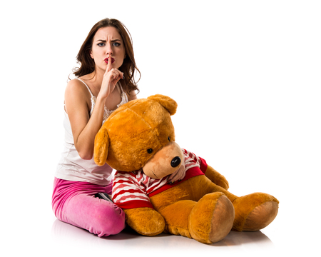gesturing: Girl with pajamas making silence gesture and playing with stuffed animal Stock Photo