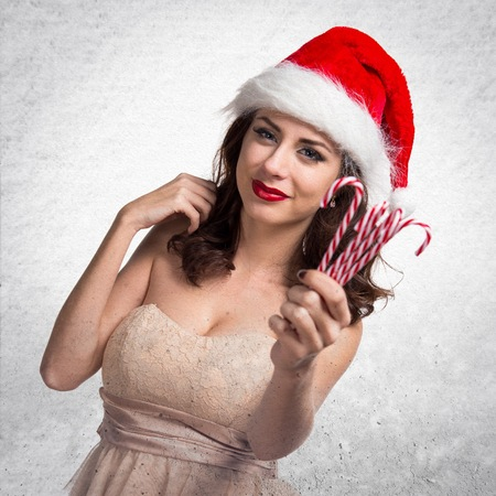 Pretty young woman holding christmas candies