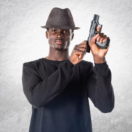 holding gun to head: Black man holding a pistol