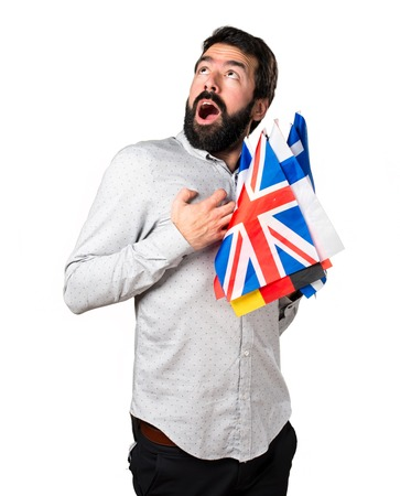 bilingual: Handsome man with beard holding many flags and in love Stock Photo