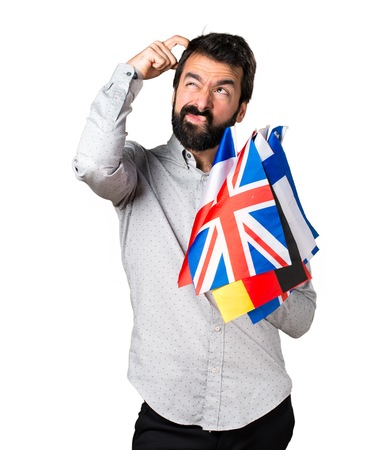 bilingual: Handsome man with beard holding many flags and having doubts Stock Photo