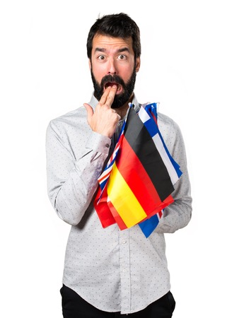 bilingual: Handsome man with beard holding many flags and making vomiting gesture