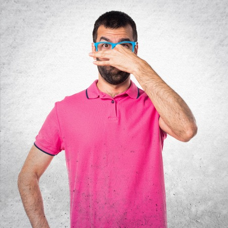 Man with colorful clothes doing smelling bad gesture on grey textured background