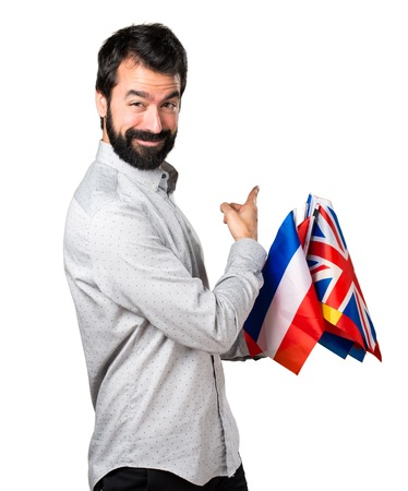 bilingual: Handsome man with beard holding many flags and pointing back