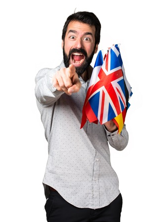 bilingual: Handsome man with beard holding many flags and pointing to the front