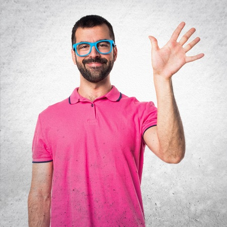 Man with colorful clothes saluting on grey textured background