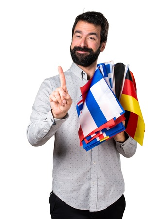 bilingual: Handsome man with beard holding many flags and counting one