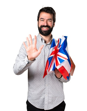 bilingual: Handsome man with beard holding many flags and five