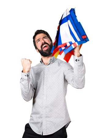 bilingual: Lucky handsome man with beard holding many flags Stock Photo